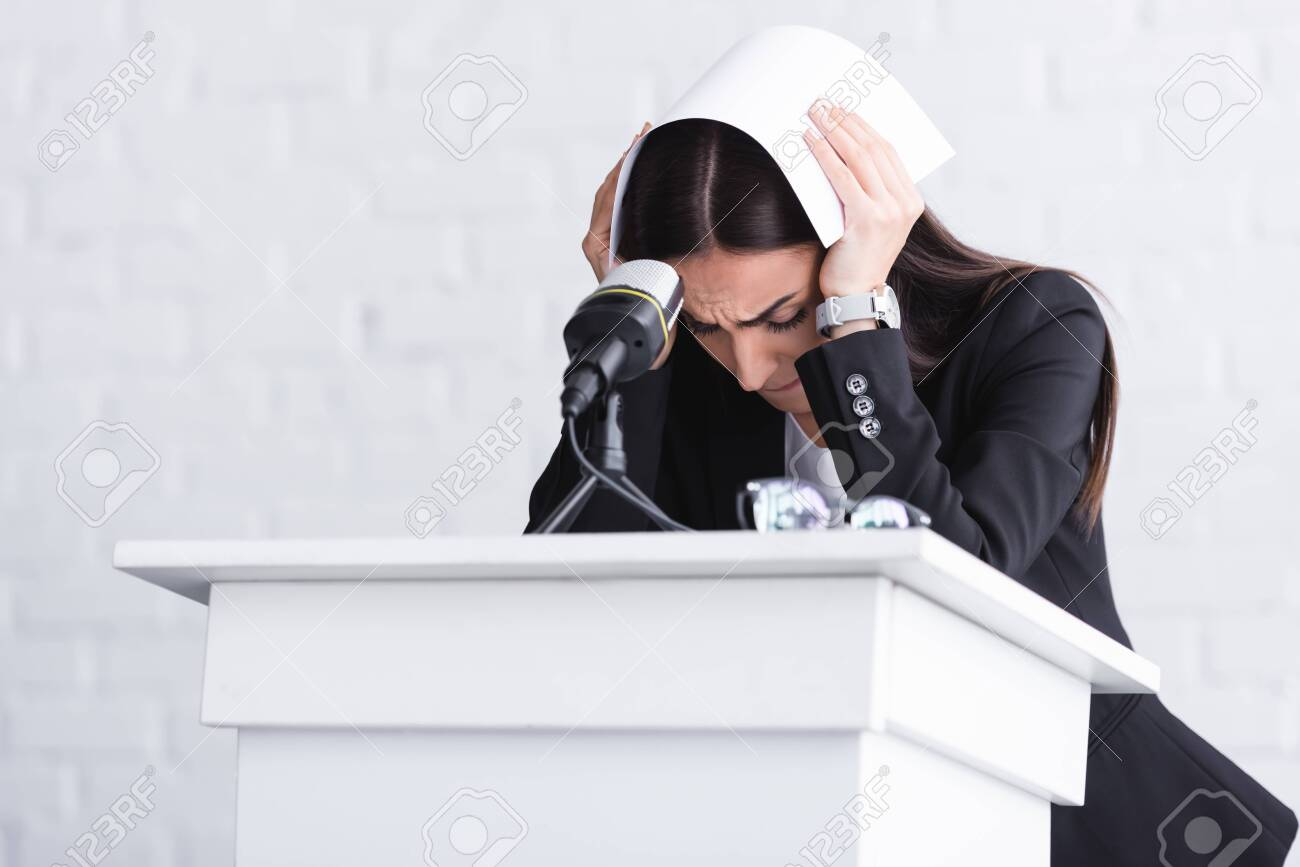 young lecturer, suffering from fear of public speaking, standing on podium tribune and covering head with paper - 130326207