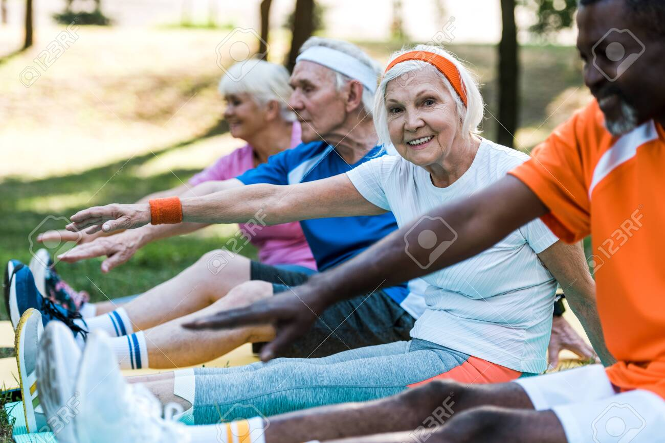 selective focus of multicultural retired women and men in sportswear exercising on fitness mats - 130106083