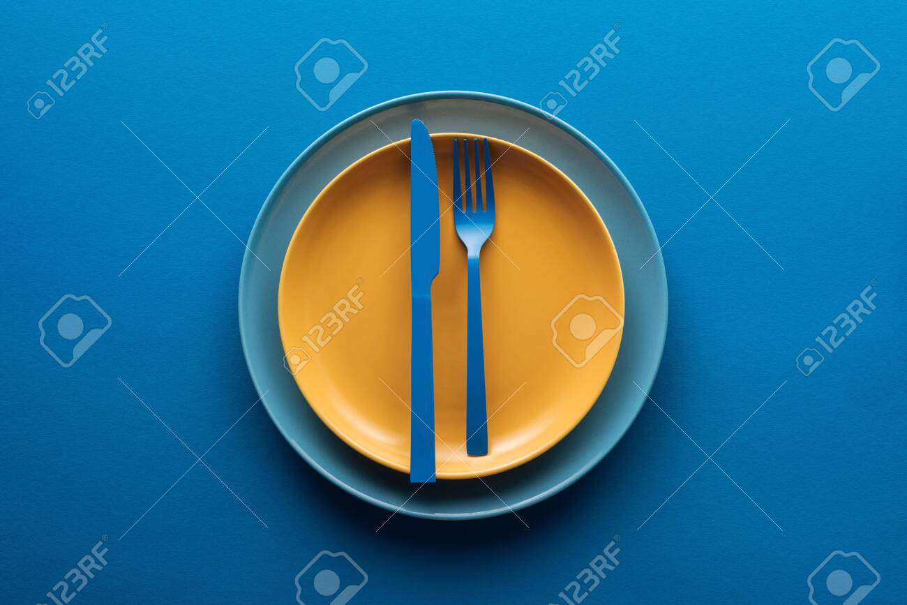 top view of blue plastic knife and fork on yellow plate above another plate on blue background - 130305228