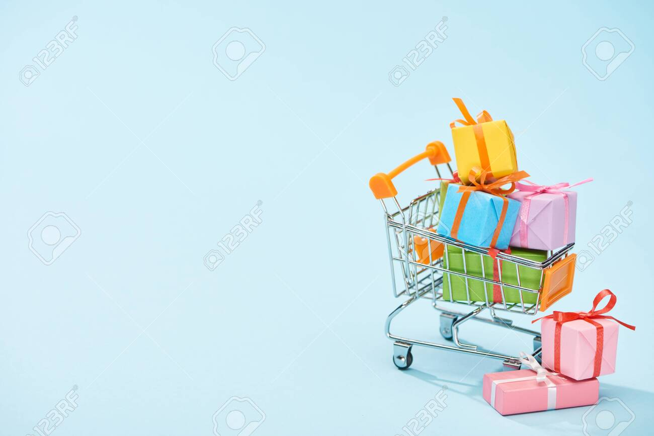 festive wrapped presents in shopping cart on blue background with copy space - 130549673