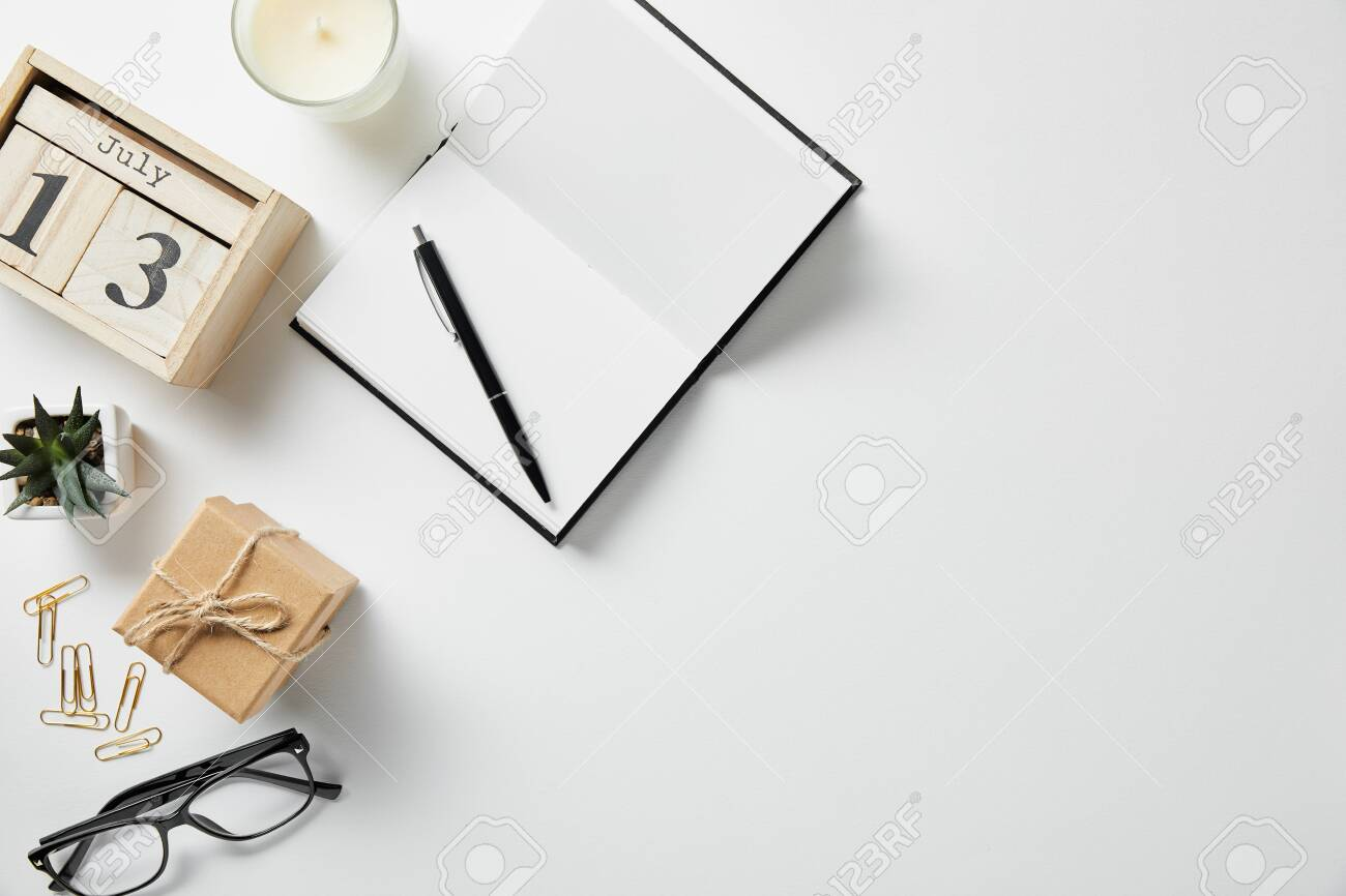 top view of blocks with numbers and letters, notepad, pen, glasses, plant and candle on white surface - 130499459