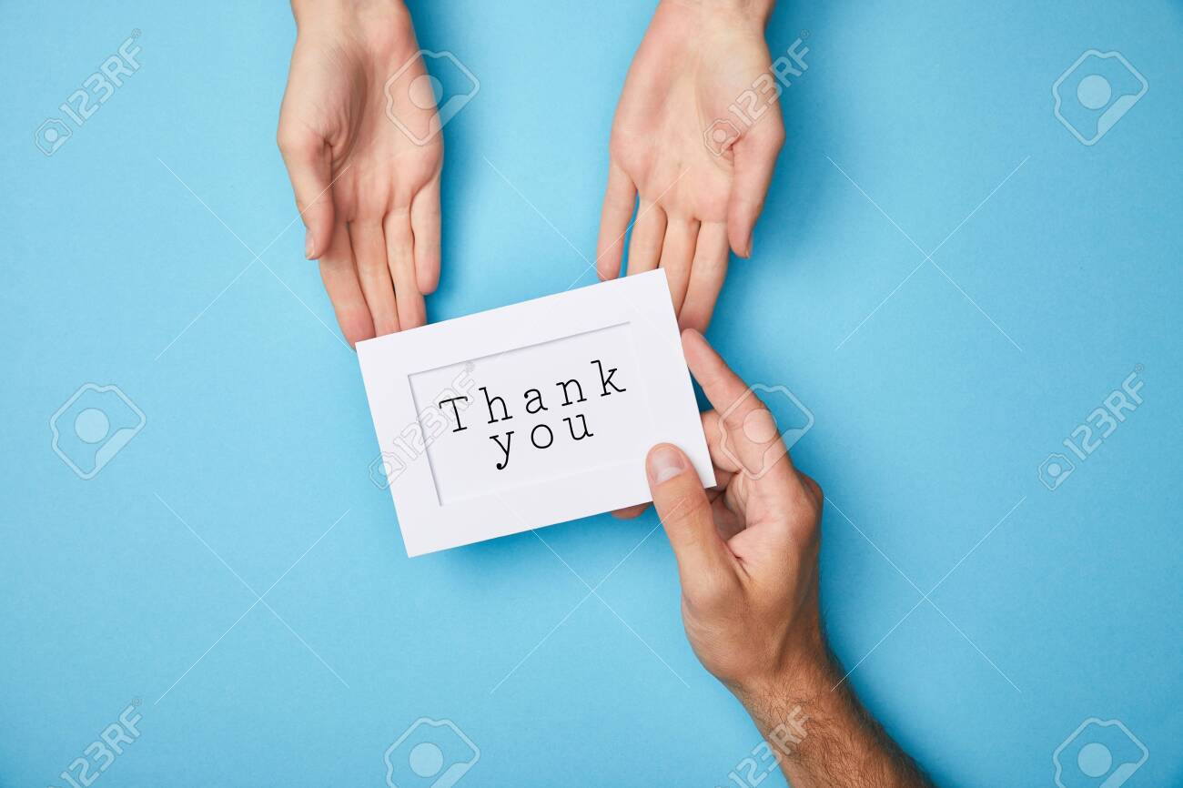 cropped view of man giving white card in frame with thank you lettering to woman on blue background - 130575491