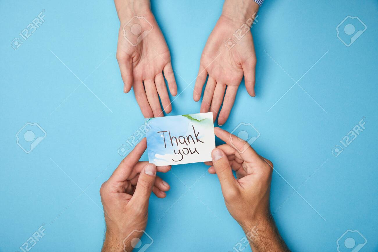 cropped view of man giving greeting card with thank you lettering to woman on blue background - 130575427