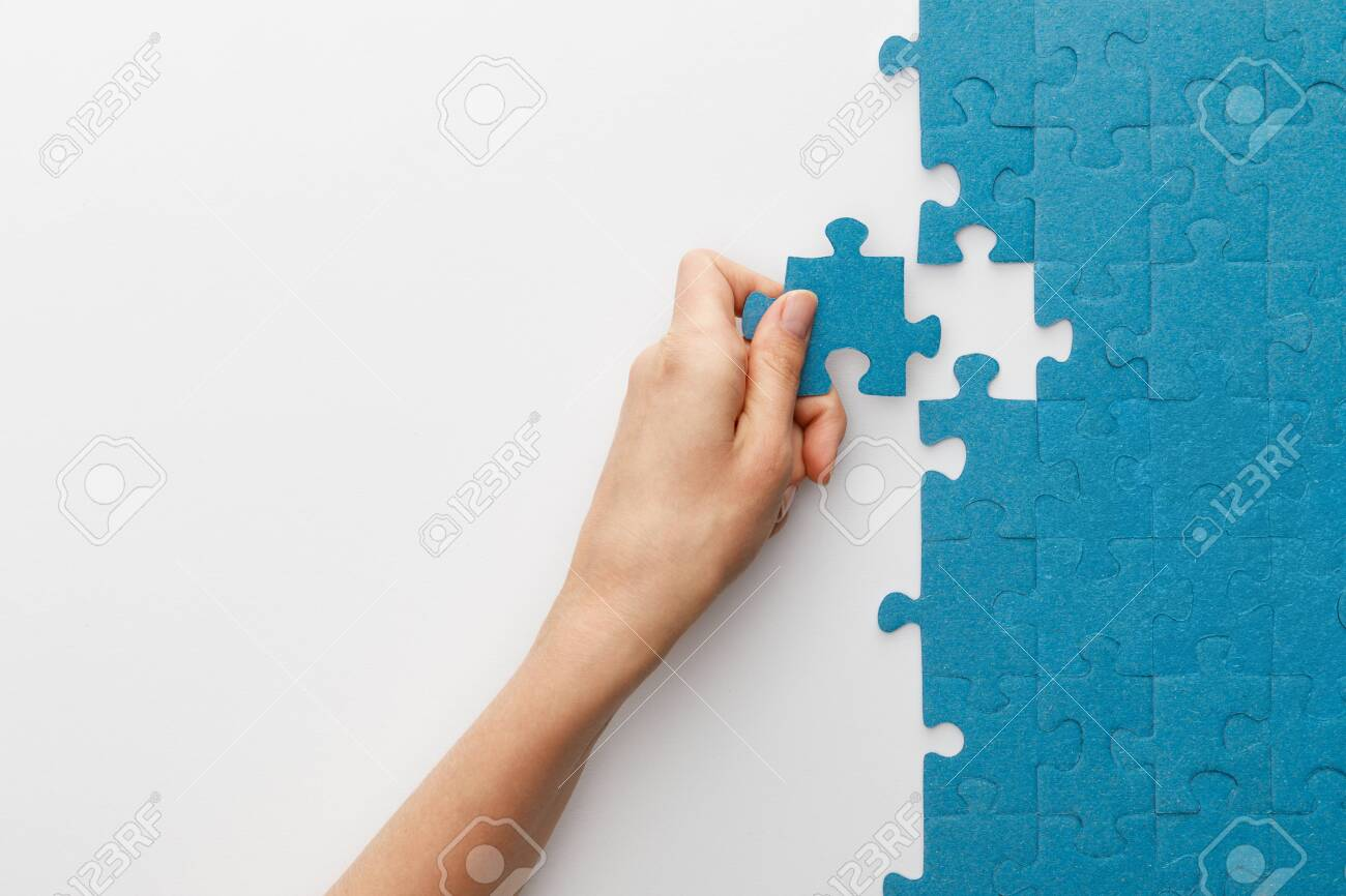 cropped view of woman attaching blue jigsaw puzzle on white background - 130574728