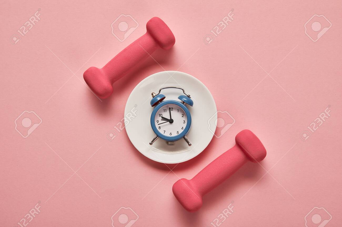top view of dumbbells and plate with toy alarm clock on pink background - 130573554