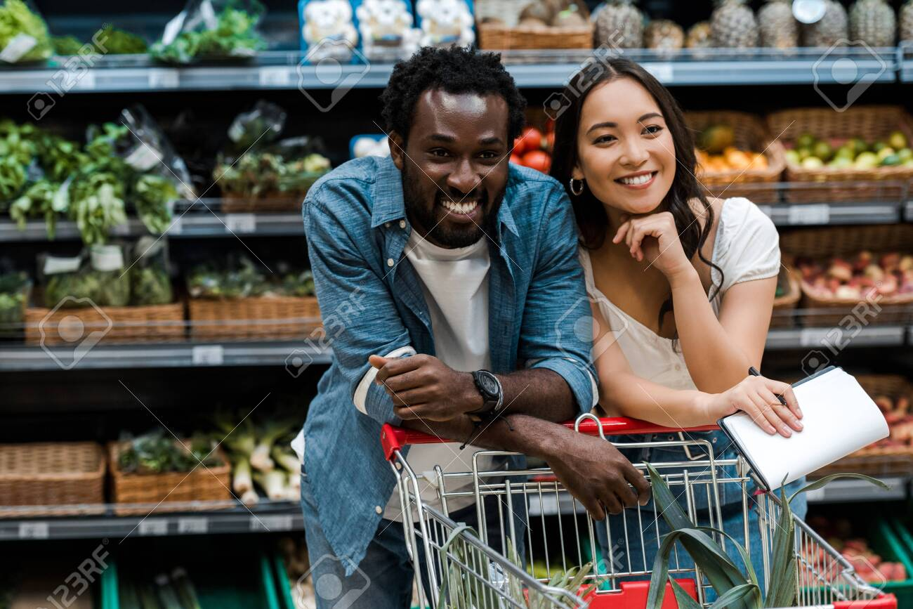 cheerful interracial couple smiling in supermarket near shopping cart - 132266730