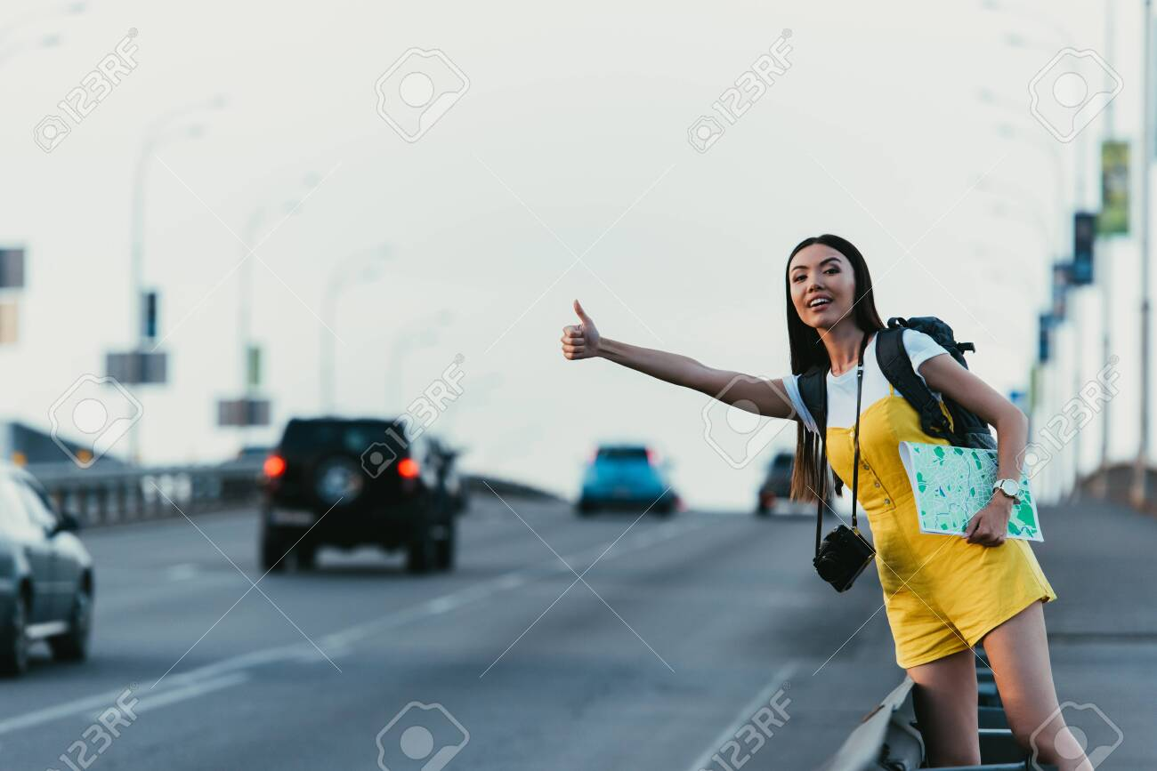 beautiful and asian woman in yellow overalls hitchhiking and holding map - 132354498