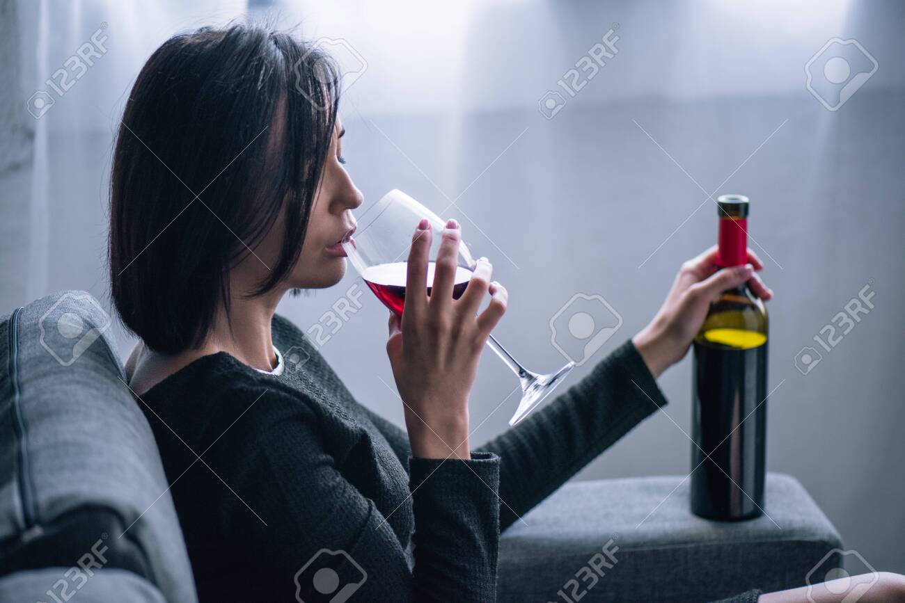depressed lonely woman sitting on couch and drinking wine at home - 132356093