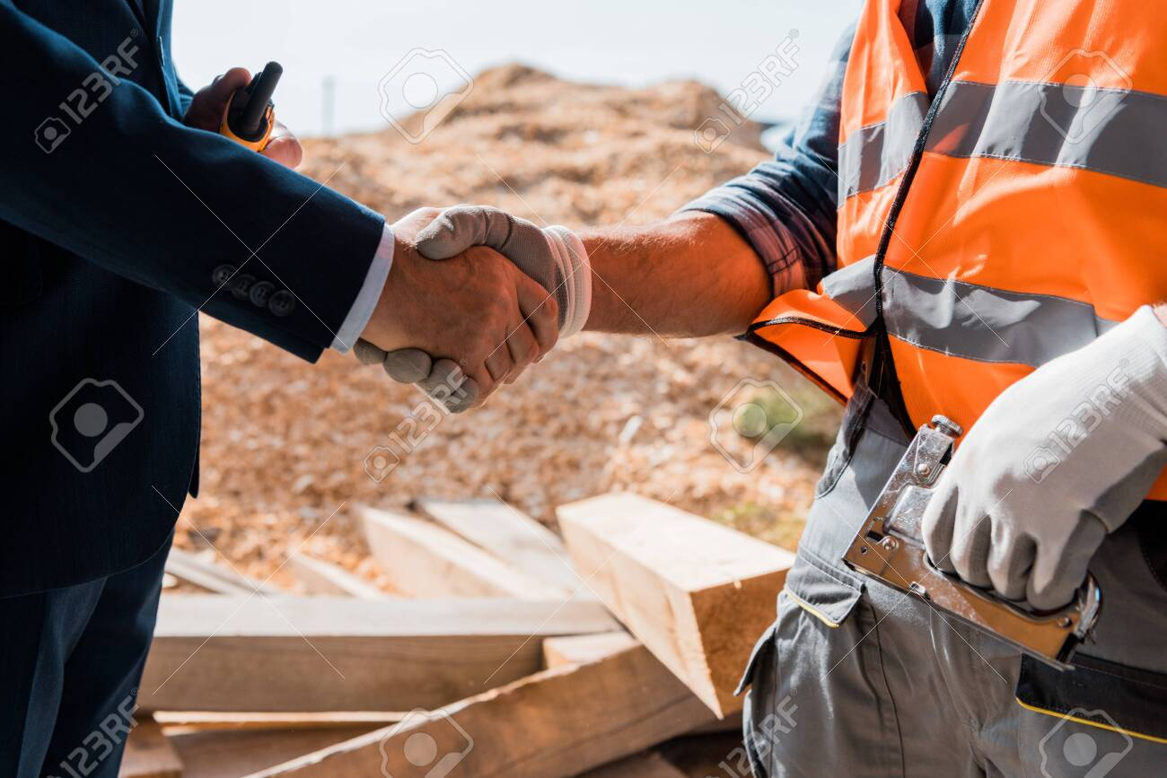 cropped view of constructor and businessman shaking hands - 131182878