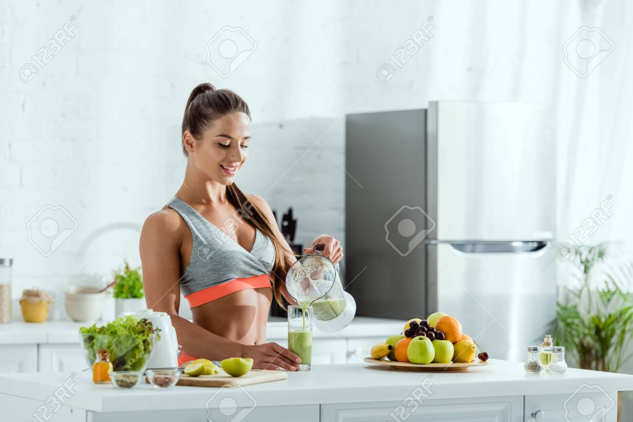 happy woman with sportswear pouring smoothie in glass near fruits - 131260419