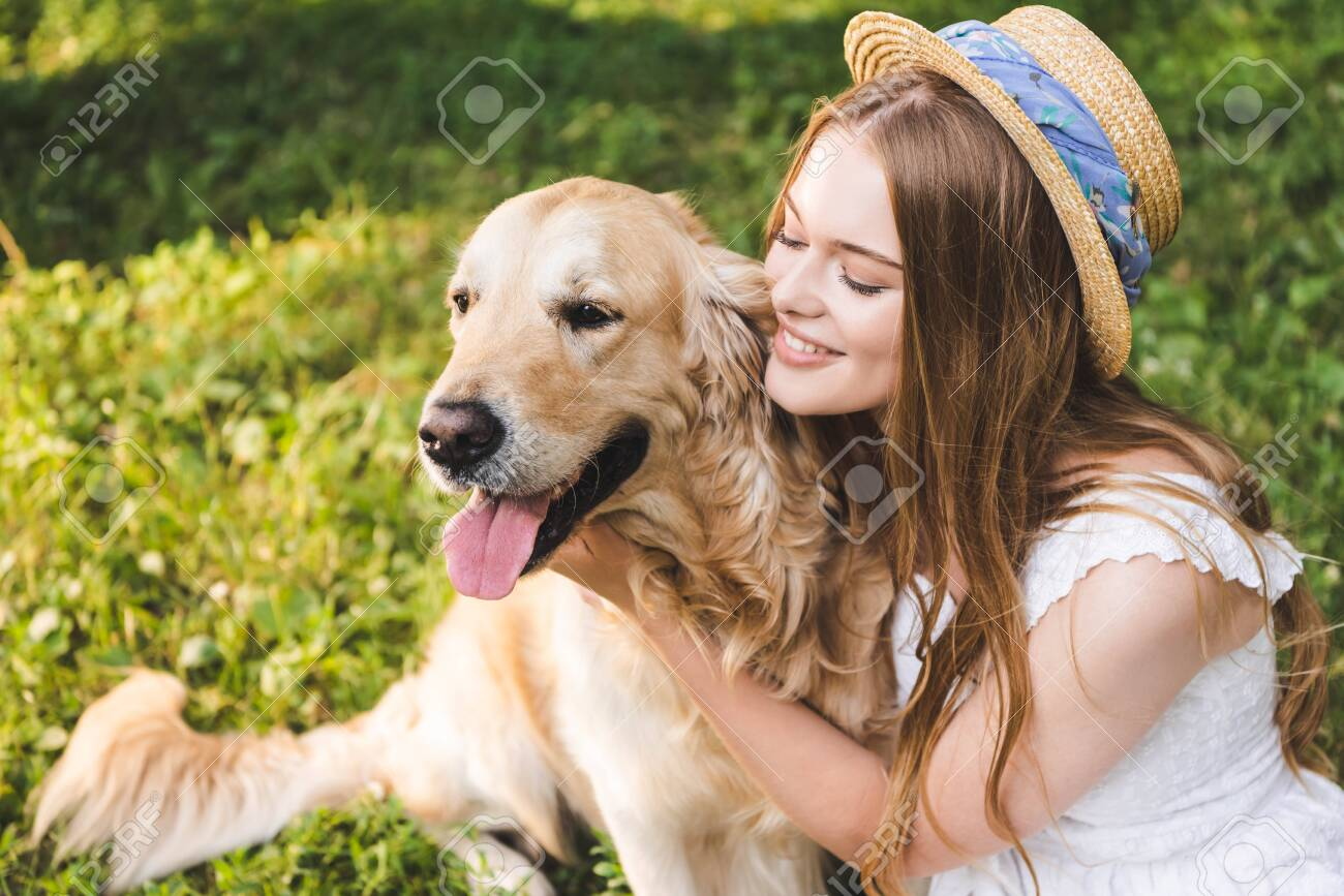 beautiful girl in white dress and straw hat hugging golden retriever while sitting on meadow and looking at dog - 131261680