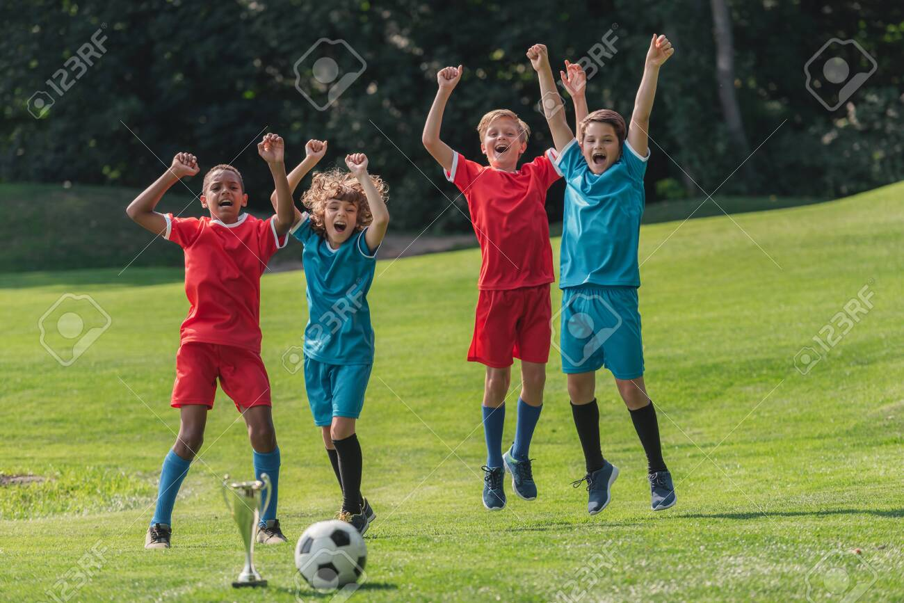happy multicultural gesturing near trophy and football - 131260253