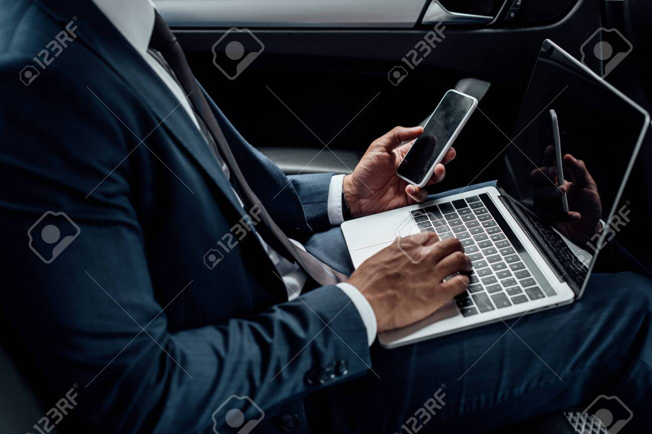cropped view of african american businessman using laptop and smartphone in car - 131819490