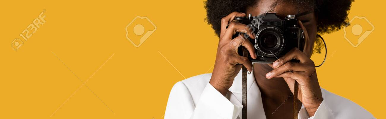 panoramic shot of curly african american woman covering face while taking photo isolated on orange - 132695815