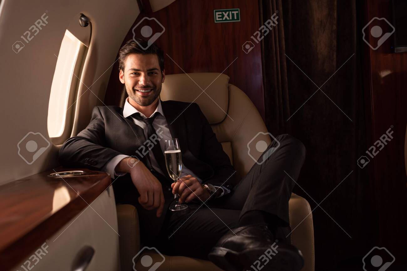handsome smiling man holding glass of champagne in plane - 132946146