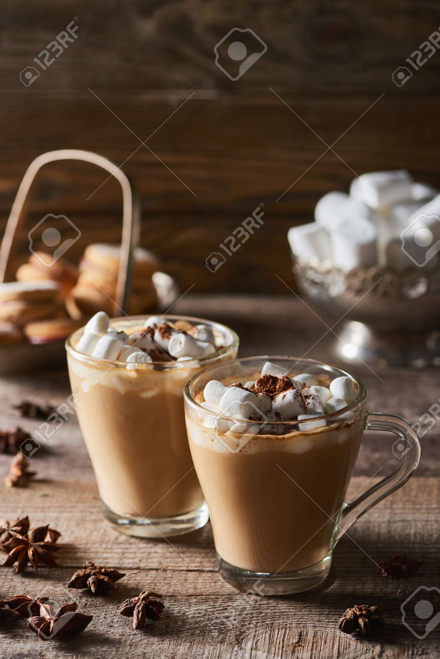 cacao with marshmallow in mugs near anise on wooden table - 133861508