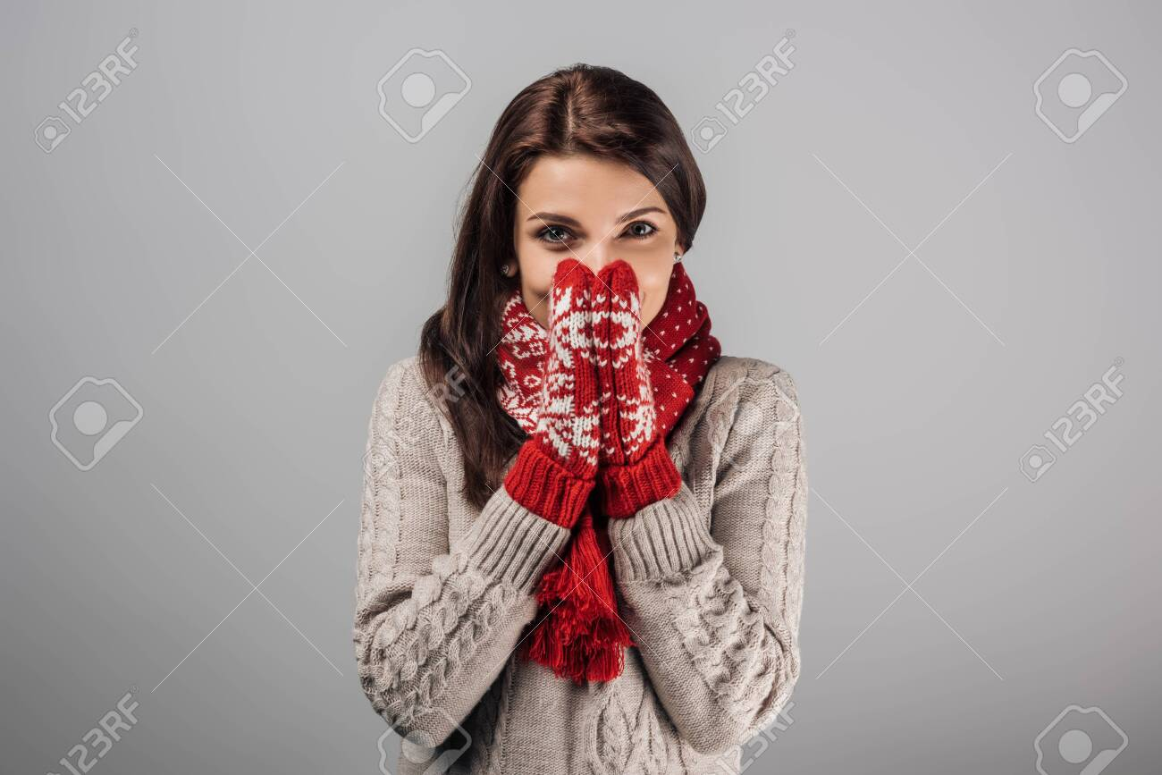 woman in red gloves and scarf covering face isolated on grey - 133839225