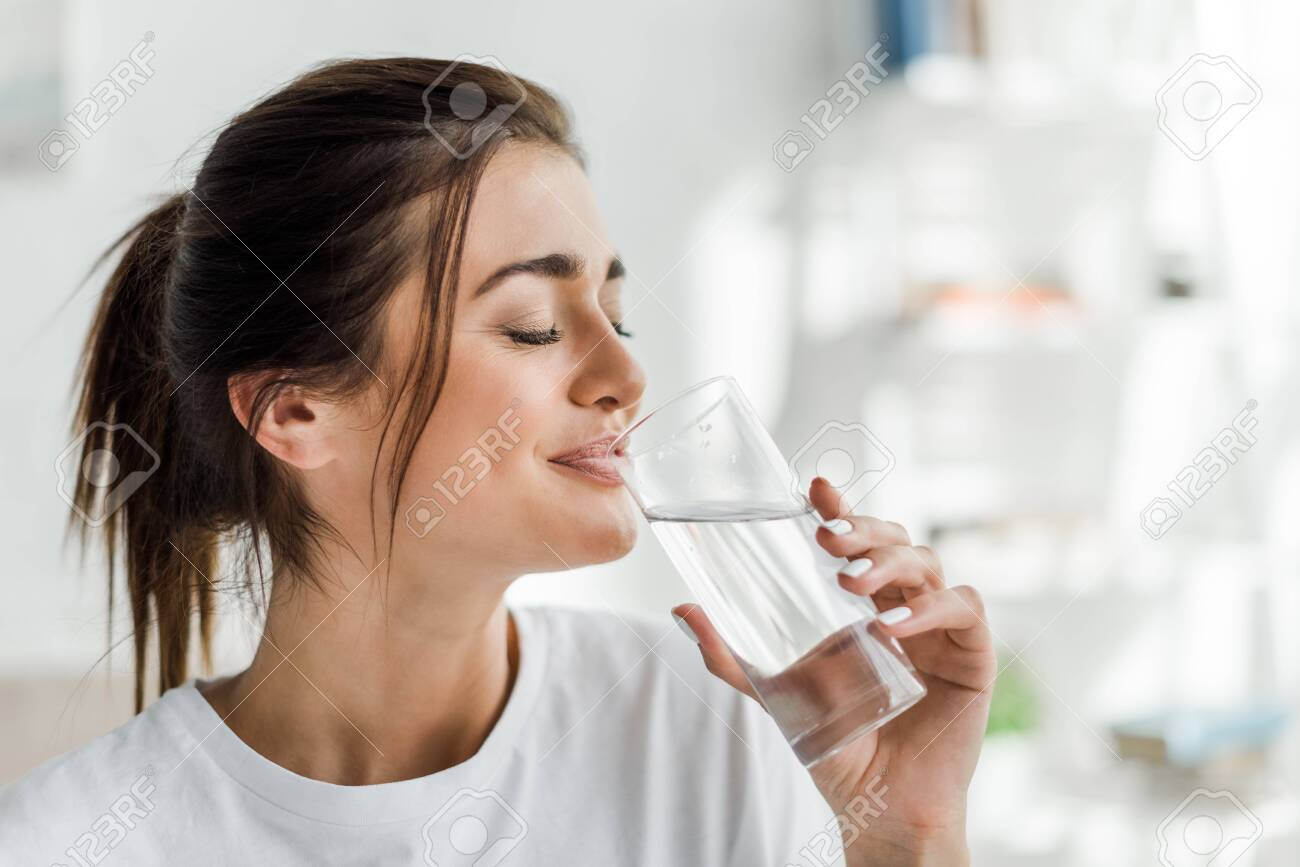 smiling girl holding drinking water from glass in the morning - 134003917