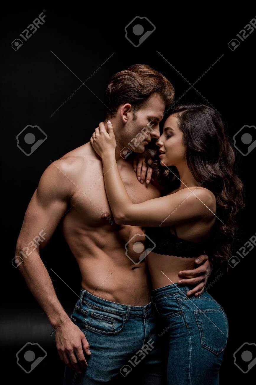 beautiful seductive couple hugging, isolated on black - 134010603
