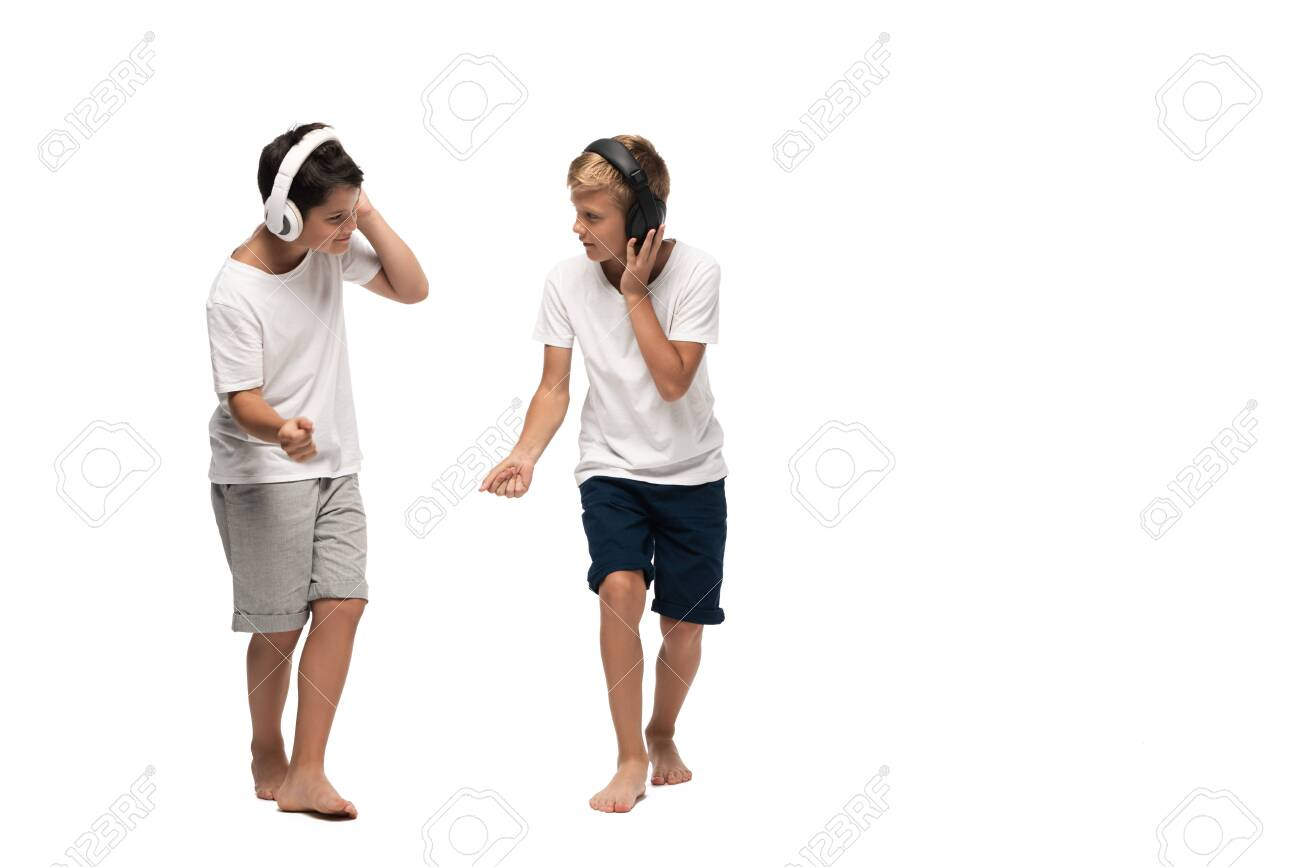 two brothers listening music in headphones and dancing on white background - 134010884