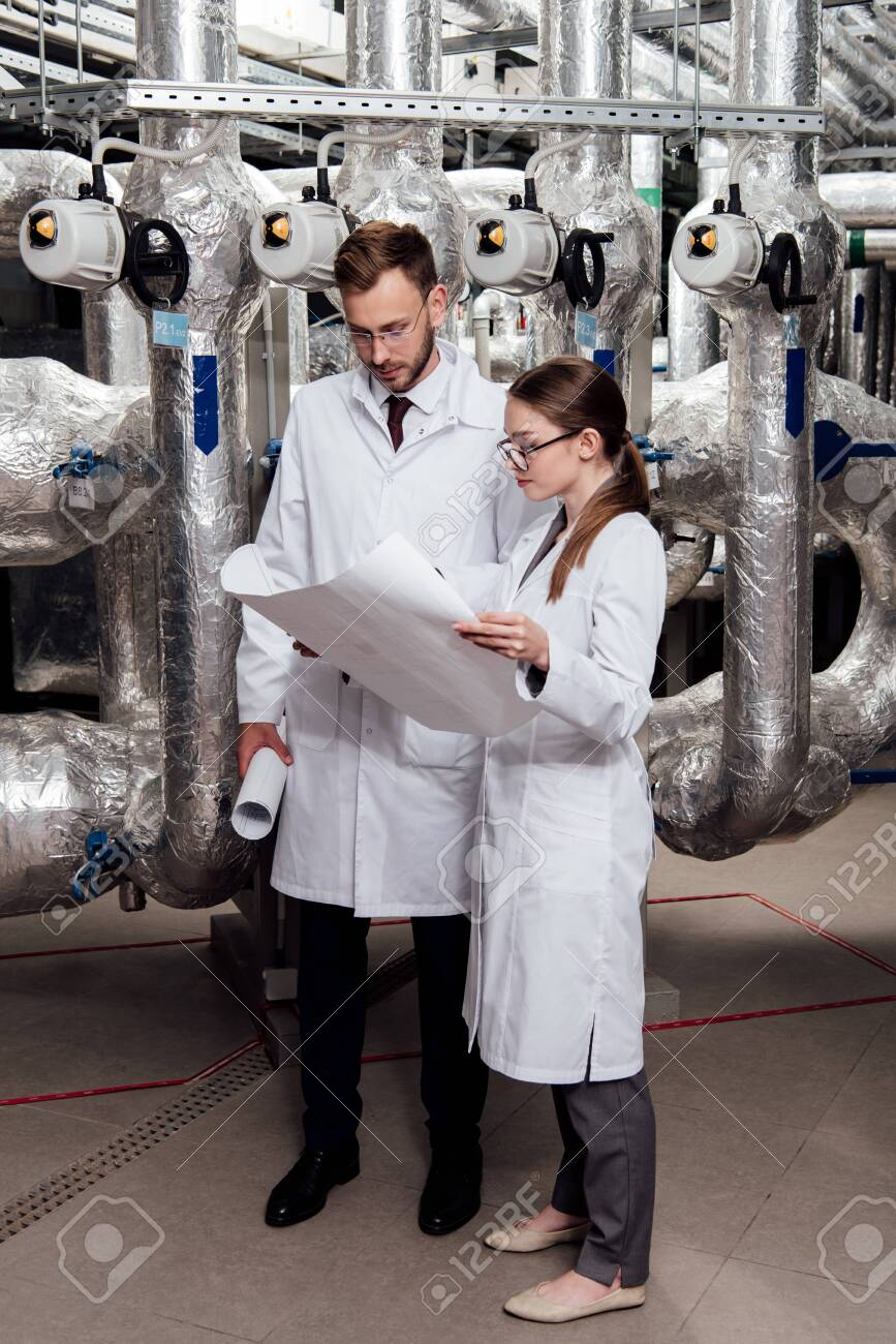 engineers in glasses and white coats looking at blueprint near air compressor system - 134011065
