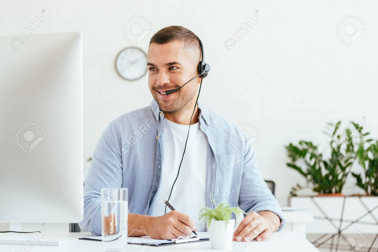 cheerful broker in headset looking at computer monitor and holding pen - 134015409