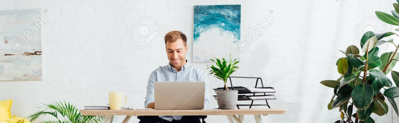 Smiling freelancer using laptop at desk in living room, panoramic shot - 134204839