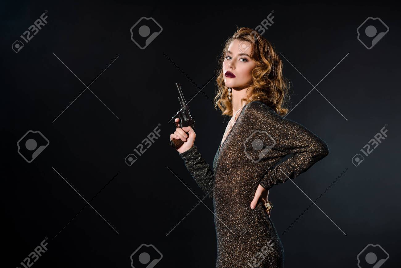 dangerous and attractive girl holding gun while standing with hand on hip isolated on black - 134636171
