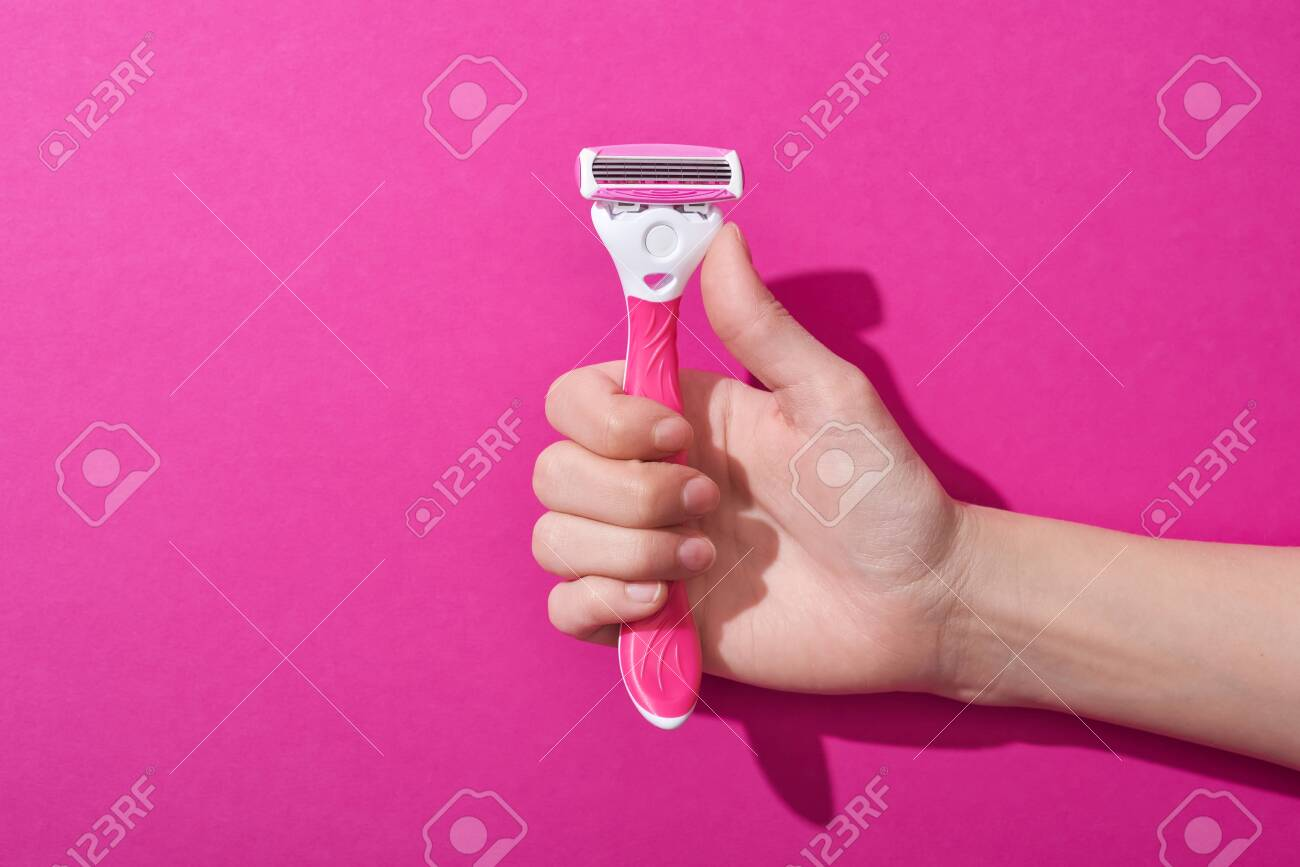 cropped view of woman holding razor on pink background - 134812848