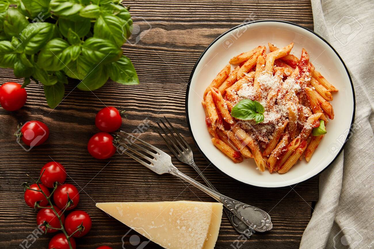 top view of tasty bolognese pasta with tomato sauce and Parmesan in white plate near ingredients and cutlery on wooden table - 134818436