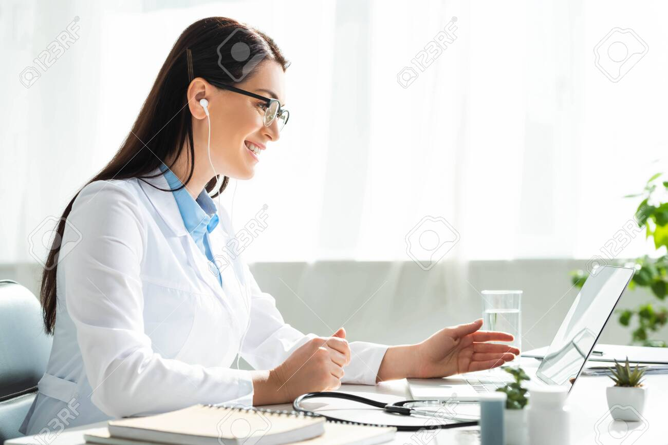 positive doctor in earphones having online consultation with patient on laptop in clinic office - 134984775