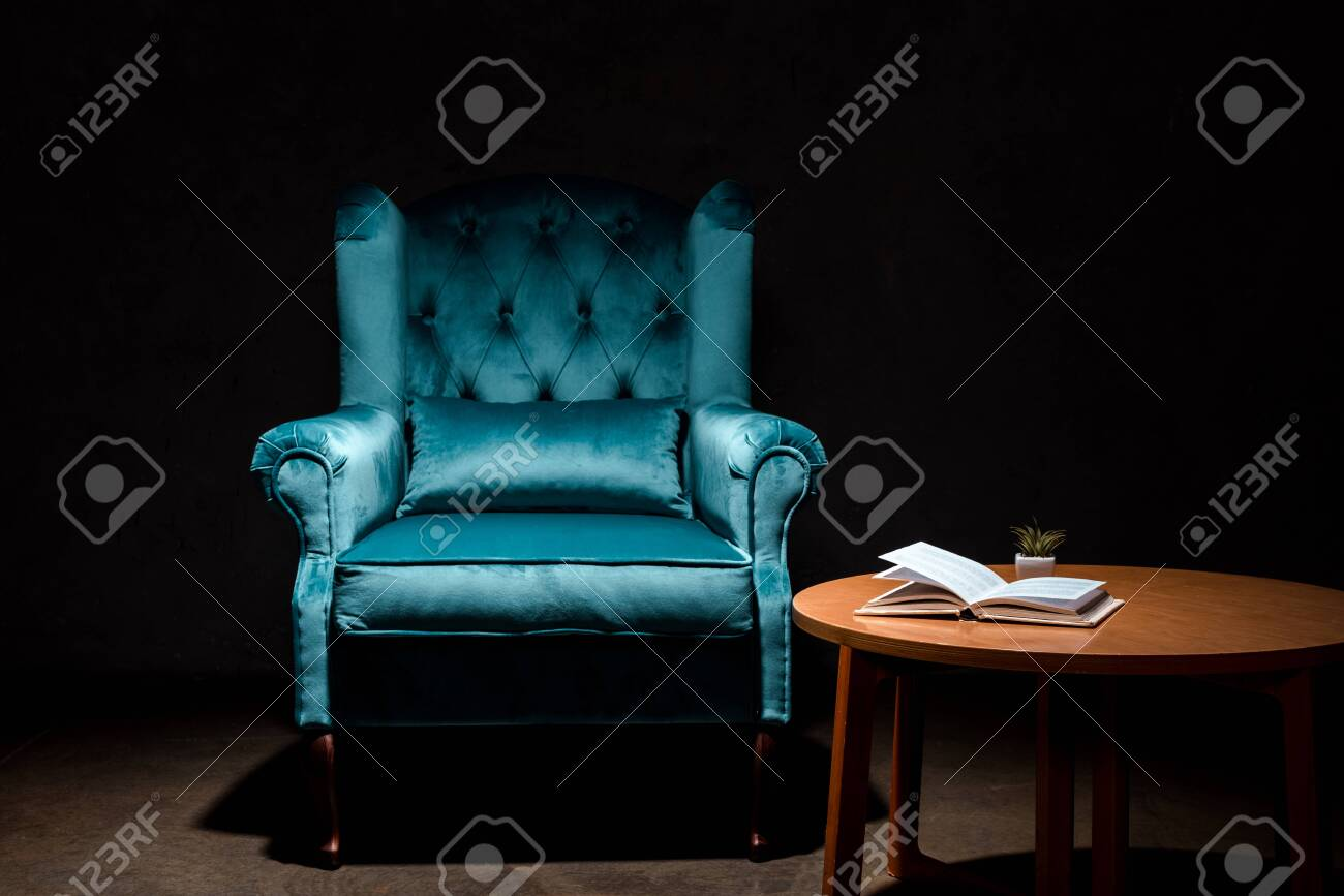 elegant velour blue armchair near wooden table with book isolated on black - 135647045