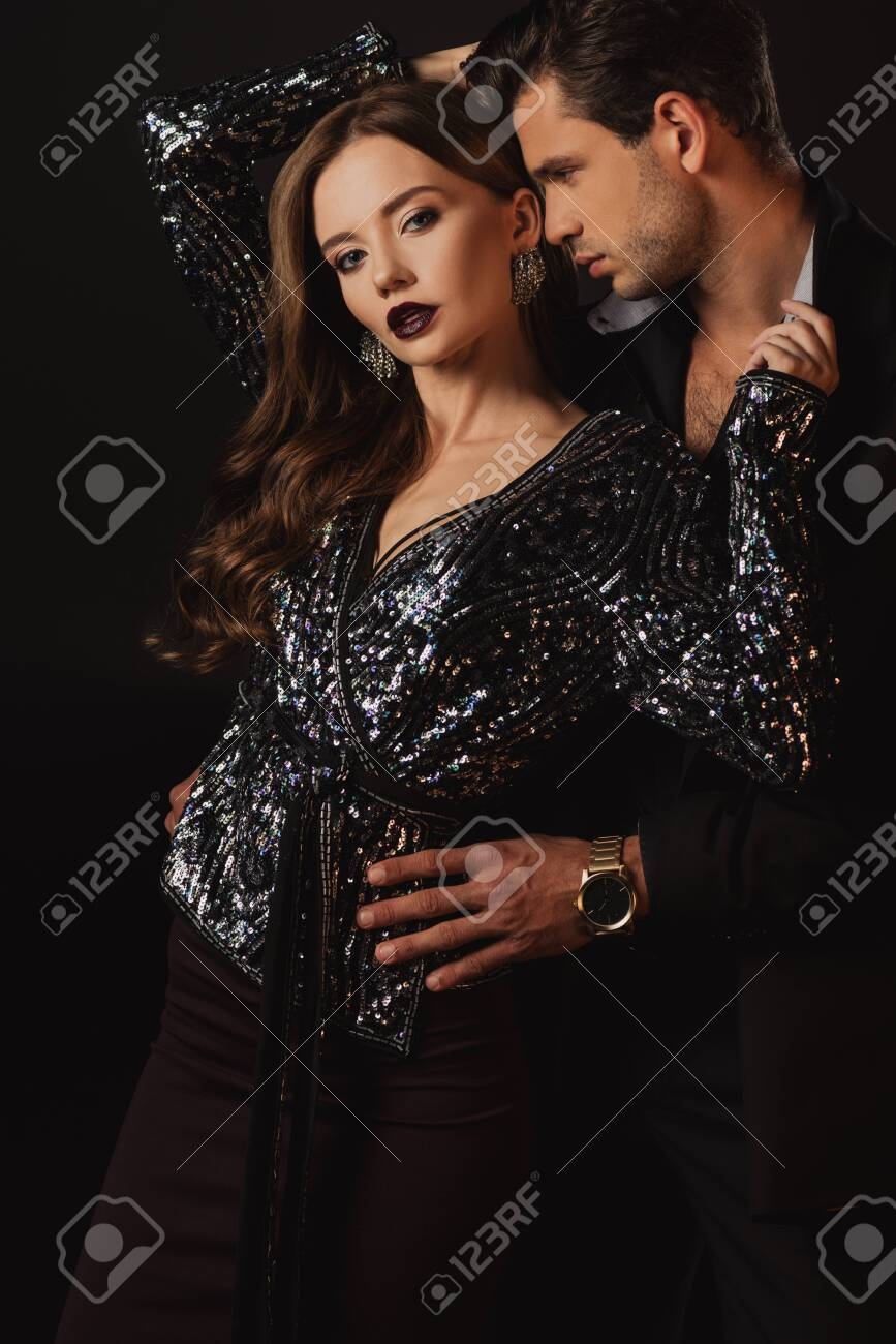 handsome man in suit hugging attractive woman isolated on black - 135698992