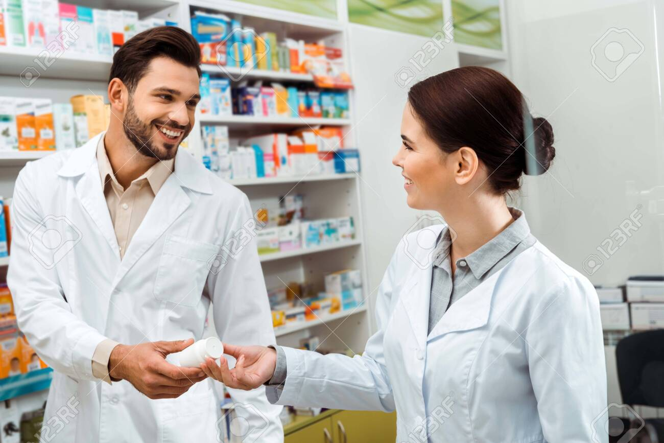 Smiling pharmacist giving to colleague jar with pills in pharmacy - 137561527
