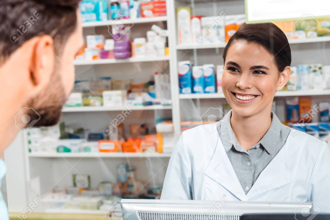 Selective focus of druggist smiling to customer at pharmacy counter - 137660950