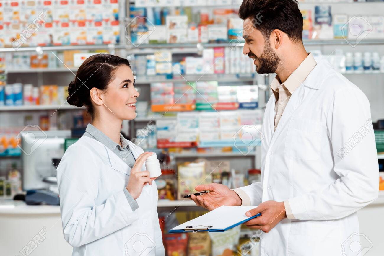 Side view of pharmacists with pills and clipboard smiling to each other in pharmacy - 137661179