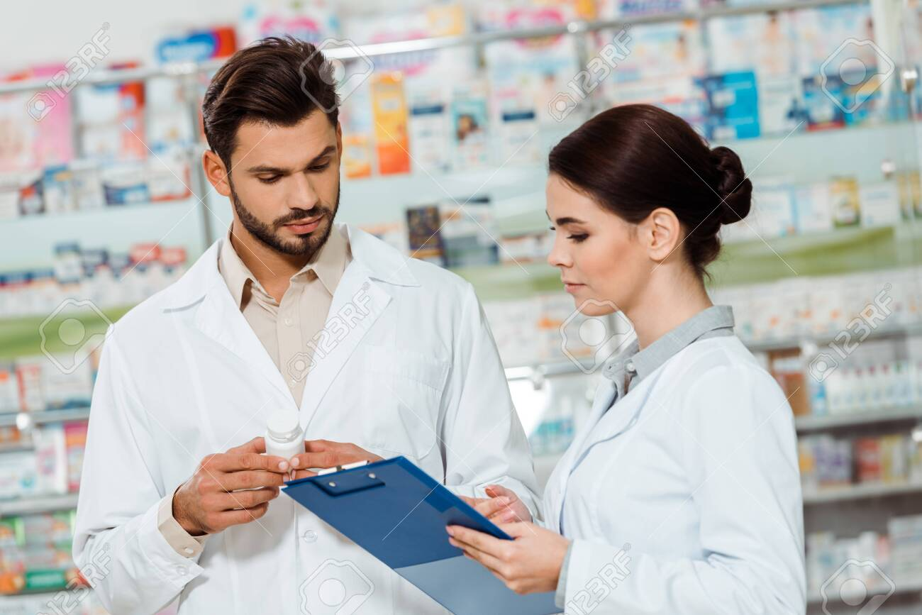 Pharmacists in white coats with pills and clipboard by drugstore showcase - 137760297