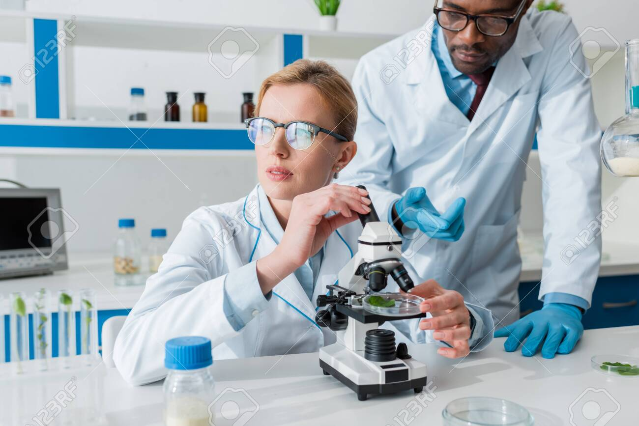 Multicultural biologists in white coats using microscope in lab - 137479697
