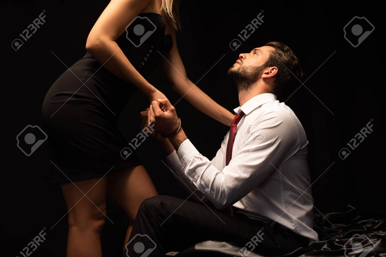 beautiful passionate couple of lovers playing with handcuffs on bed in dark room - 137726417