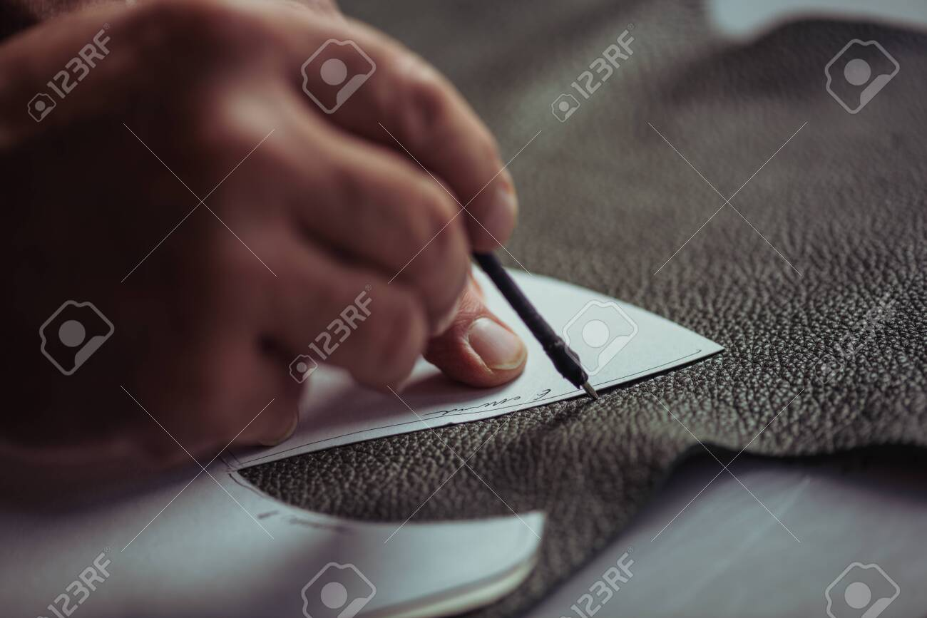 cropped view of cobbler marking leather with special pen near template - 139504508