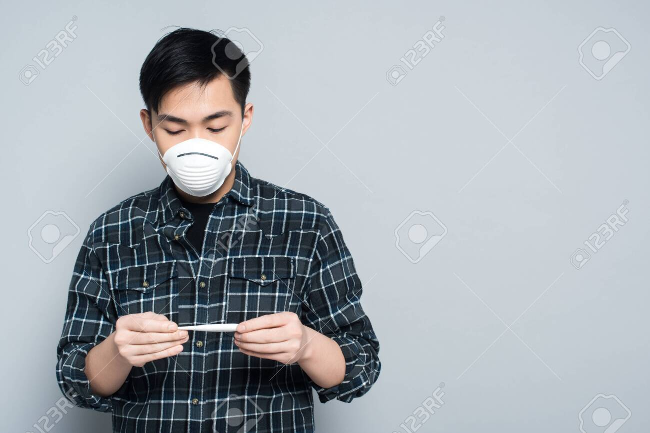 young asian man in respirator mask looking at thermometer on grey background - 140556145