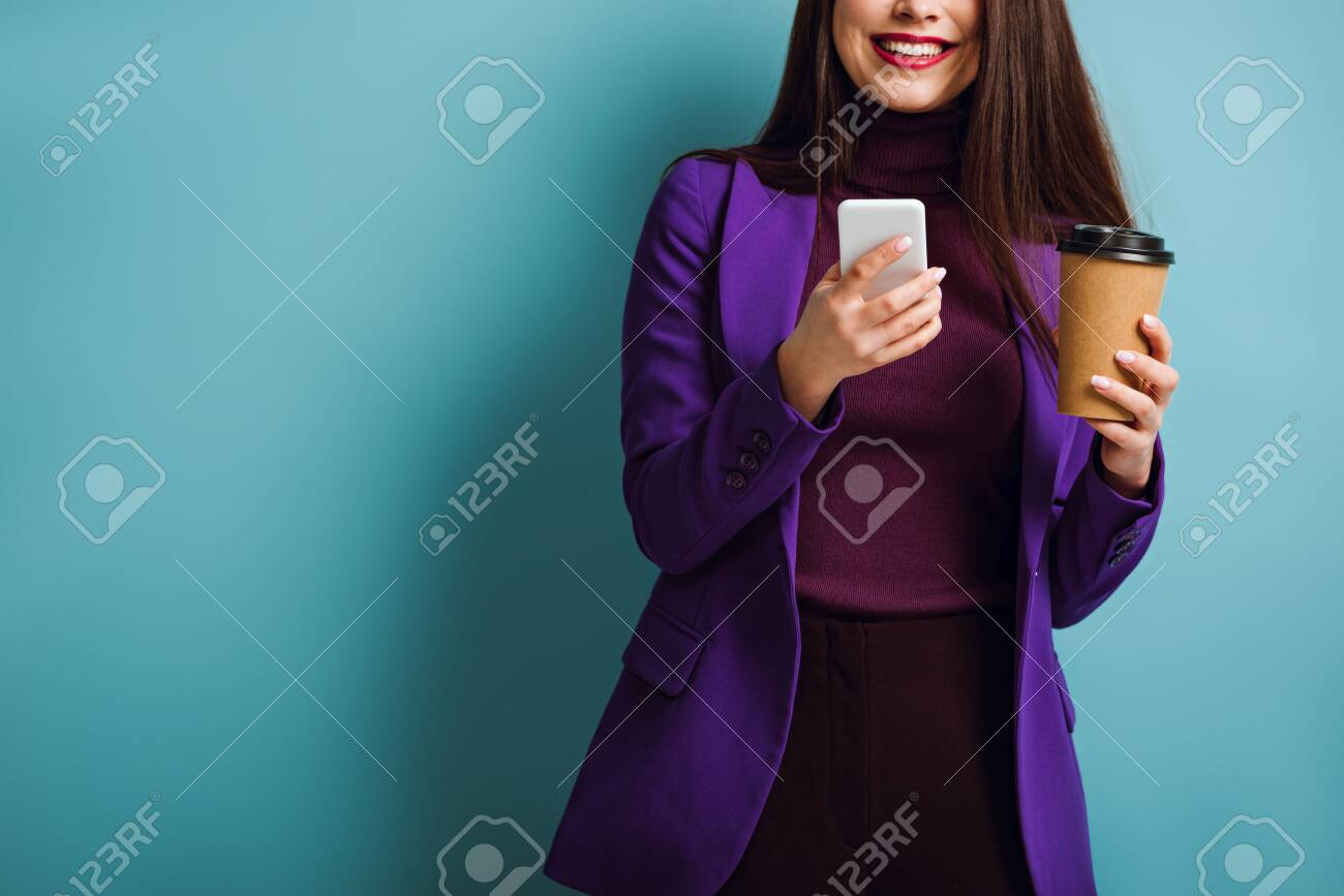 cropped view of smiling girl chatting on smartphone while holding coffee to go on blue background - 141041408