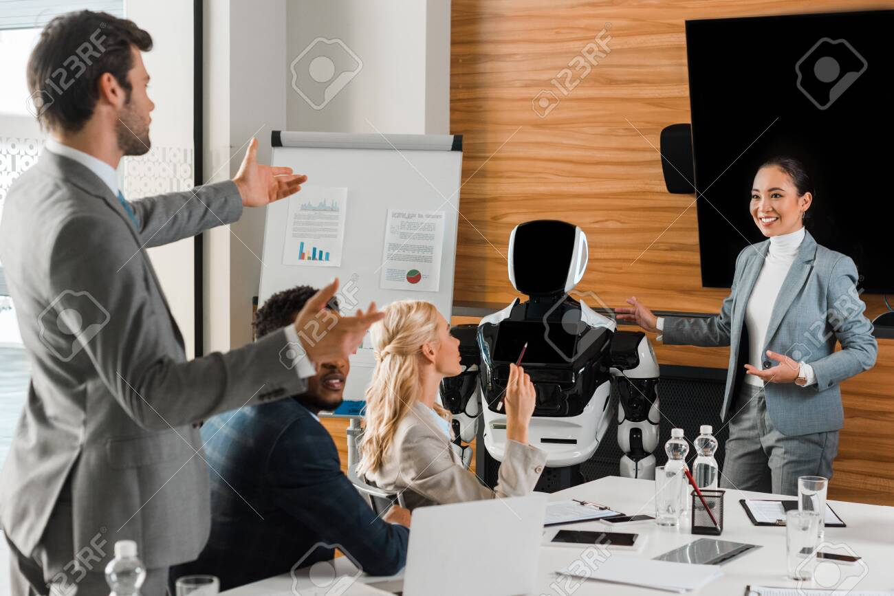 attractive asian businesswoman pointing with hands at robot near colleagues in conference hall - 141256779
