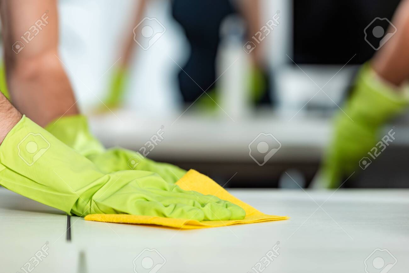 cropped view of man in rubber gloves cleaning desk surface with rag - 142861394