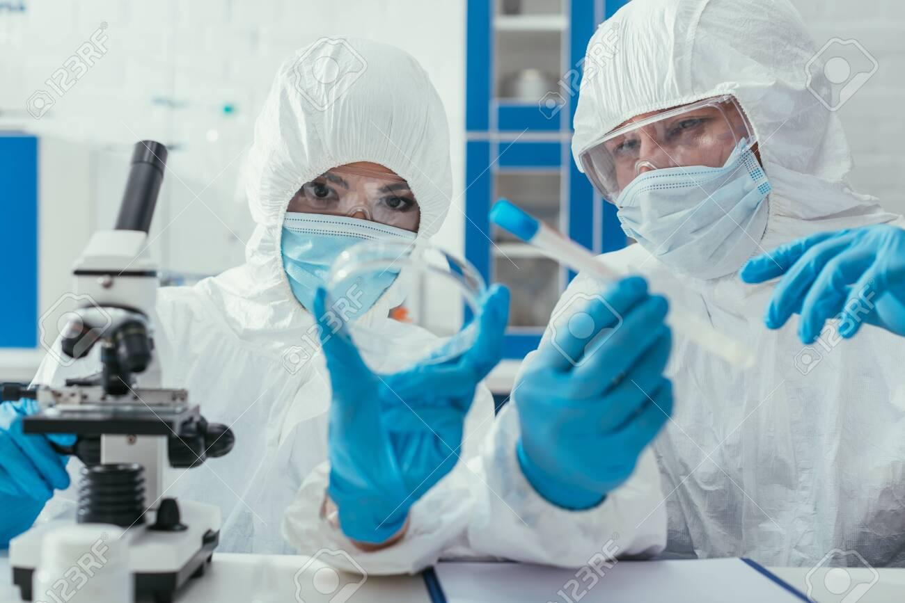 biochemists holding test tube and petri dish near microscope - 144106929