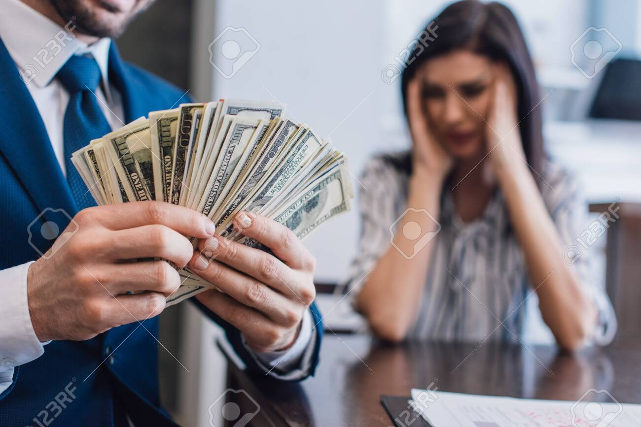Selective focus of collector with money near stressed woman at table in room - 146929958