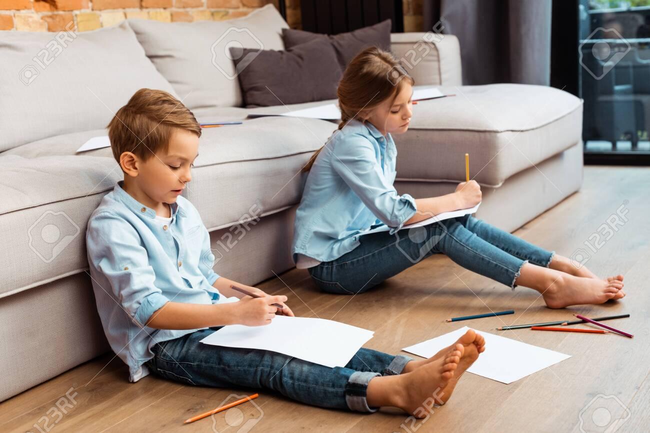 cute siblings sitting on floor and drawing in living room - 147503435