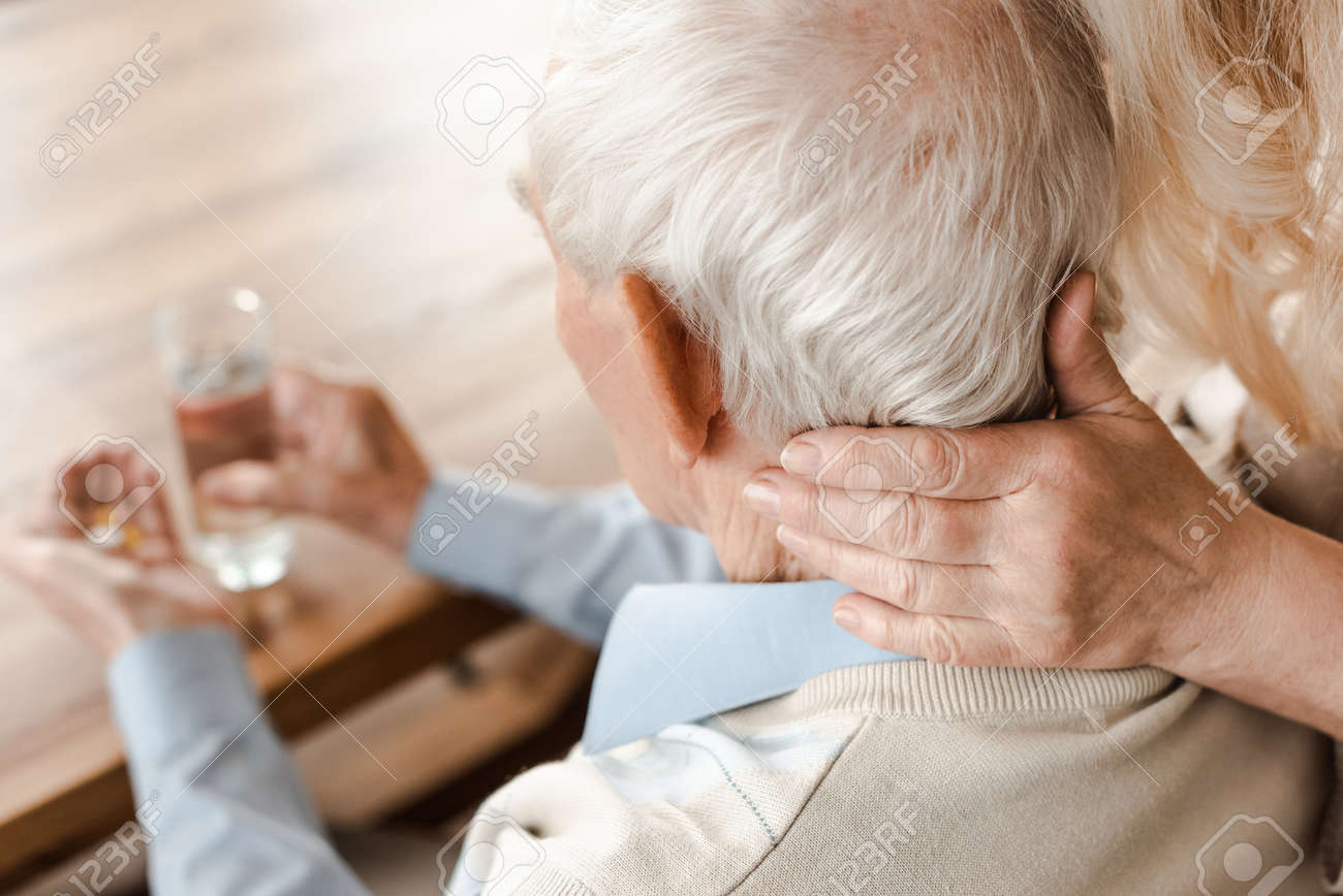 ill elderly couple with pills and glass of water at home on self isolation, selective focus - 149638176