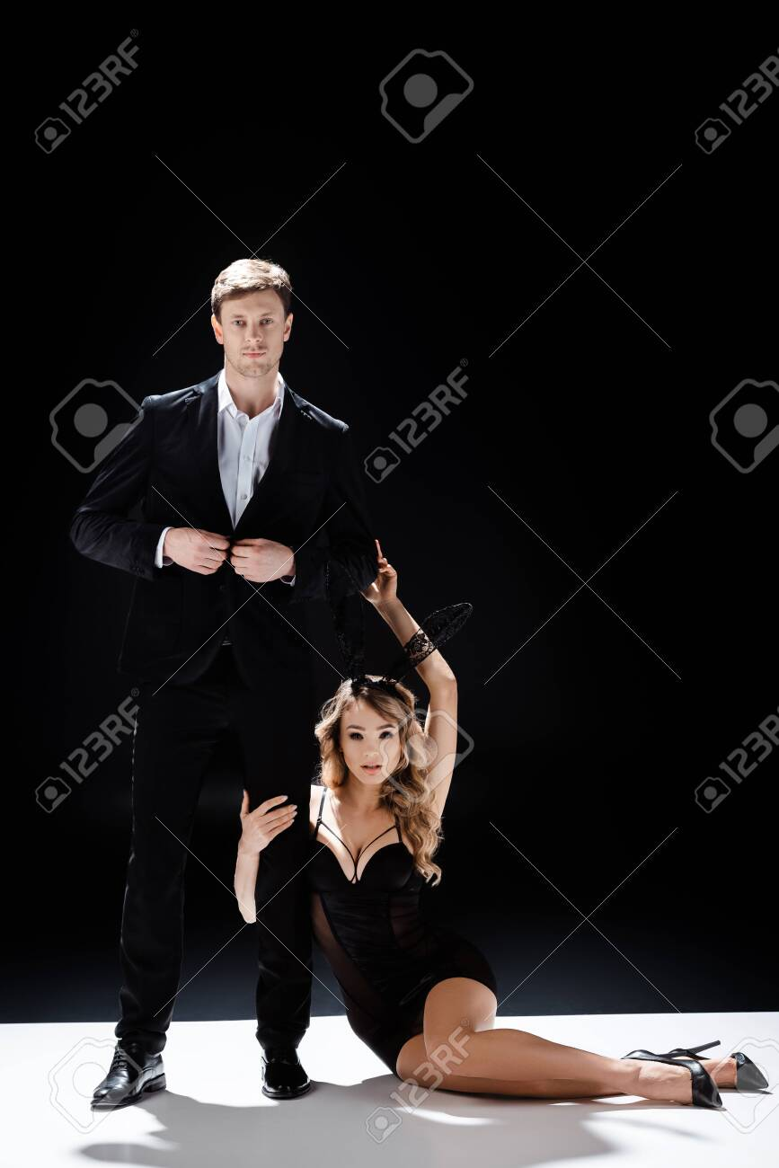 Sexy woman in bunny ears touching handsome man while sitting on white surface on black background - 149832748