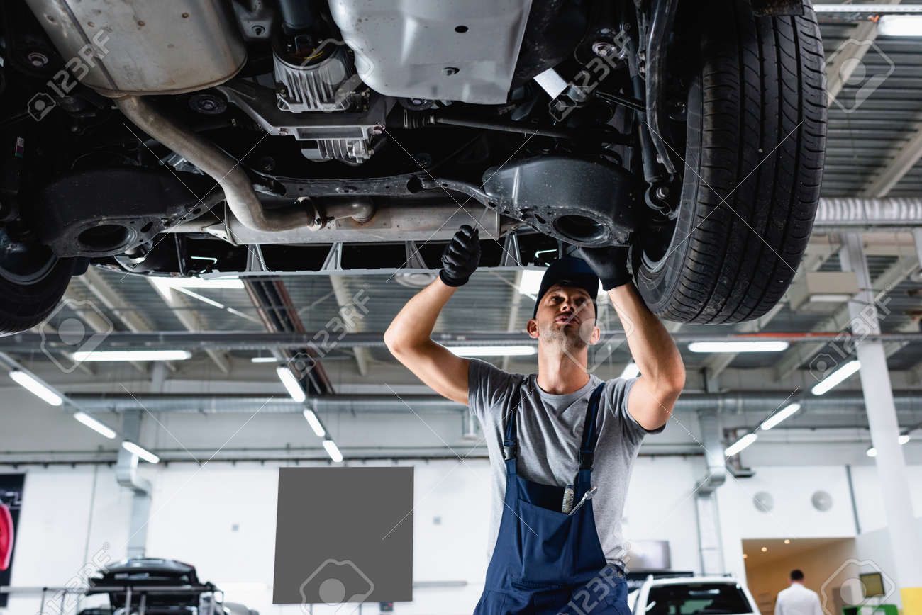 low angle view of technician in cap and overalls repairing car in service station - 152273748